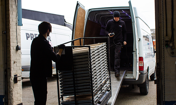 Loading the equipment in the van, ready for delivery.